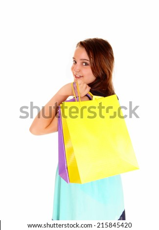 A smiling teenager girl holding up her shopping bag's, isolated on white background.  - stock photo