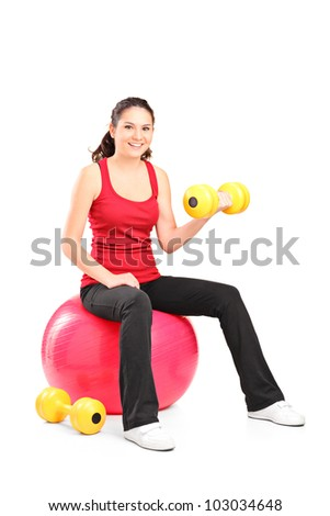 A smiling teenager lifting up a dumbbell seated on a fitness ball isolated on white background - stock photo