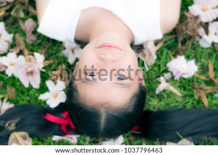A smiling ten years old asian female child girl young woman with red ribbon tie on black hair lie down on green grass with pink trumpet flower on ground. (Selective focus, Color filter apply)