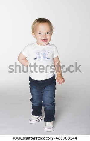 A smiling toddler girl in white t-shirt and blue jeans walking with right hand behind her back on white background