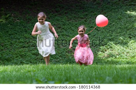 A smiling two little sisters running in the park. Surrounded by greenery - stock photo