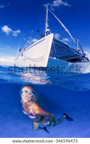 A smiling underwater model in a brightly colored bikini swimming towards the camera in very clear and very blue water