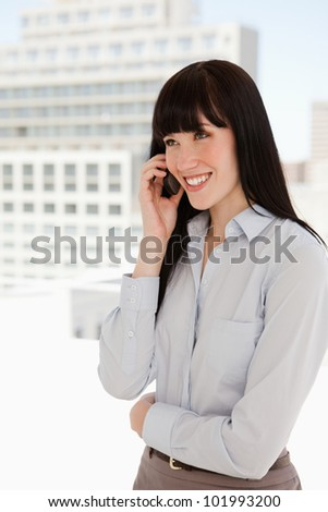 A smiling woman at work in her office takes a phone call - stock photo
