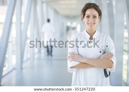 A smiling woman doctor standing in a corridor with folded arms holding a stethoscope - stock photo