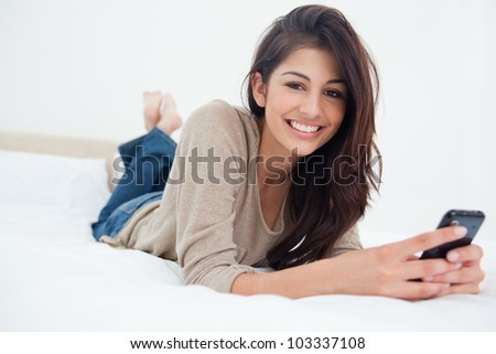 A smiling woman holds her phone in front of her as she looks forward while on the bed. - stock photo