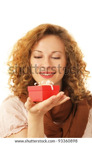 A smiling woman is holding a gift in her hand on white background