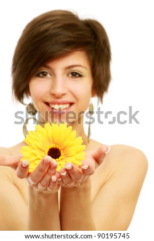 A smiling woman is holding a yellow gerbera ,focus on gerbera, over white - stock photo