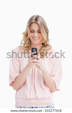 A smiling woman is looking at her mobile phone against a white background - stock photo