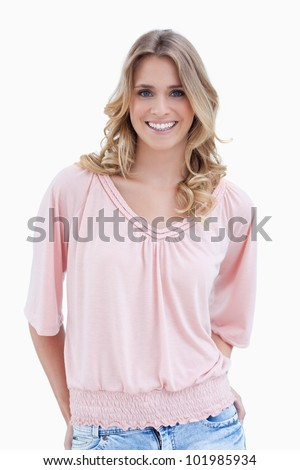 A smiling woman is standing with her arms behind her back against a white background - stock photo