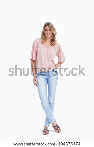 A smiling woman is standing with her legs crossed against a white background - stock photo