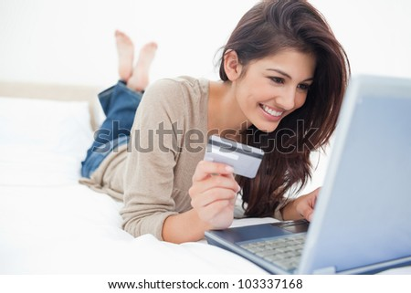 A smiling woman on her bed with laptop in front of her and credit card in hand, with crossed feet. - stock photo