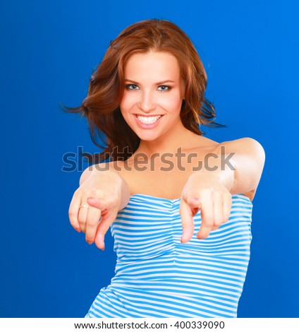 A smiling woman pointing on you, isolated on blue background - stock photo