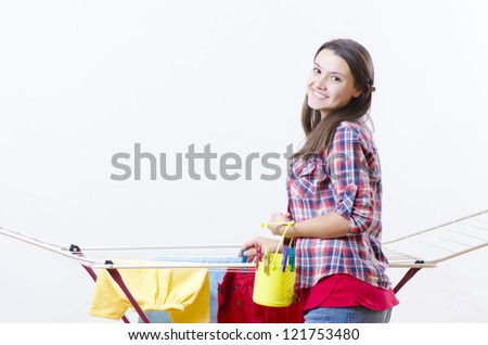 A smiling woman putting clothes to dry - stock photo