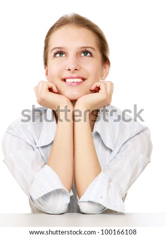 A smiling woman sitting at the desk and looking up , isolated on white - stock photo