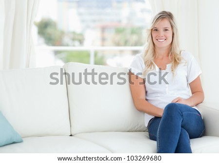 A smiling woman sitting on her couch in her house