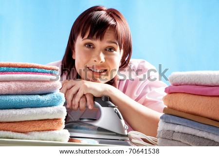 A smiling woman with an iron and heaps of ironed towels
