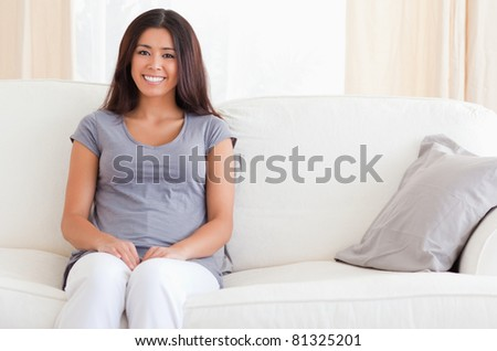A smiling woman with brunette hair is sitting on a sofa in the living room