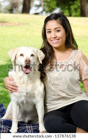 A smiling woman with her pet dog in the park.
