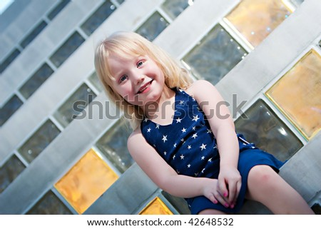 A smiling young girl sitting on steps with pink nail polish - stock photo