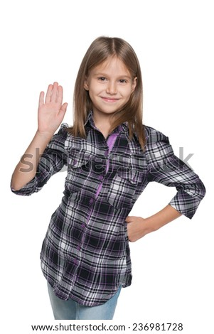 A smiling young girl stretching his right hand up on the white background