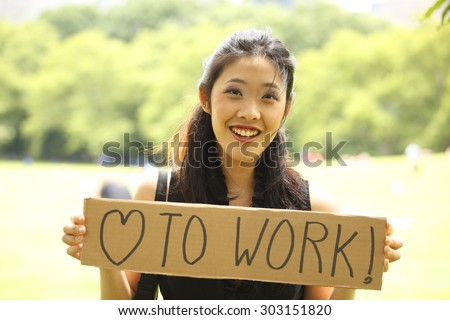 """A smiling young woman holding a """"love to work"""" sign in a park setting. - stock photo"""