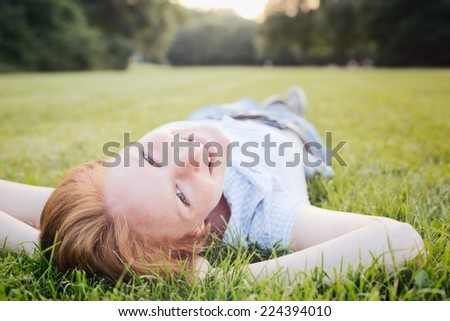 A smiling young woman lies on her back on green grass at an outdoor park on a summer afternoon and looks at the camera. - stock photo