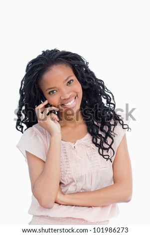 A smiling young woman looking at the camera is talking on her mobile phone