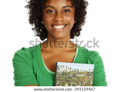 A smiling young woman looking at the viewer with a generic travel brochure clutched to her chest.