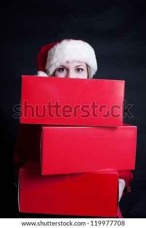 A smiling young woman with Santa Hat on holding three red blank large boxes leaving only eyes of her face showing. - stock photo