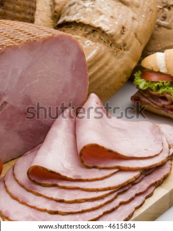 a smoked ham  piece and slices still life over a table - stock photo