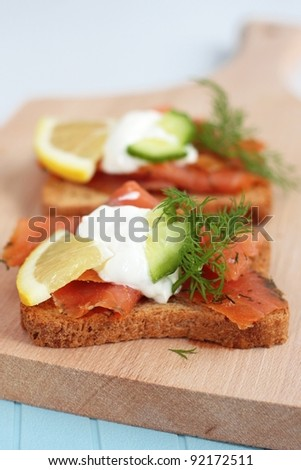A smoked salmon open sandwich on wholemeal bread. With cucumber, sour cream, lemon and dill.