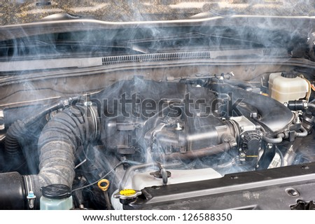 A smokey car engine shows signs of a lack of maintenance.