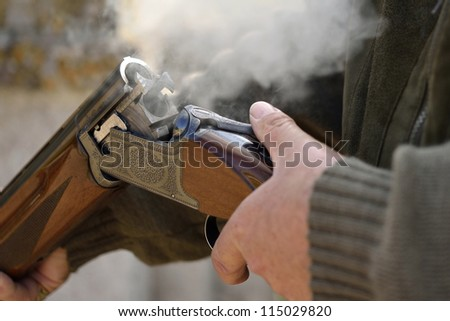 A smoking 12 bore shotgun having ejected spent a cartridge - stock photo