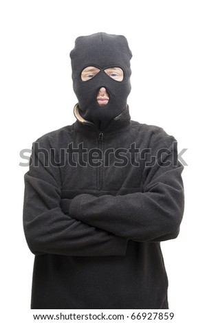 A Smug Looking Masked Assailant Stands With His Arms Crossed Front On In A Studio Portrait - stock photo