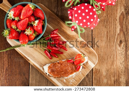 A snack on a rustic table with chili and strawberry jam - stock photo