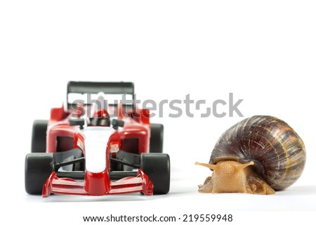 A Snail and an F1 toy car ready to race - stock photo