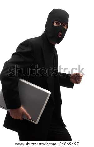 A sneaky thief wearing a black suit is walking with a laptop, isolated against a white background
