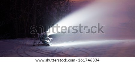 A snow cannon making snow in the winter at night - stock photo