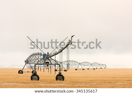 A snow covered center pivot irrigation unit sits alone in a field during winter waiting to be used again in the spring.