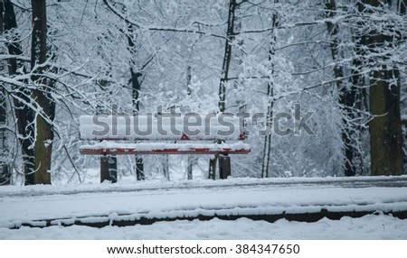 A snow covered children's bench in the park in winter.