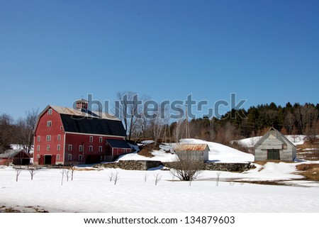 A snow covered farm and a red barn