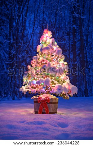 A snow covered natural spruce Christmas tree with illuminated colorful lights sits in an old aged wine barrel pot outside in a snowy forest during the winter season at night time.  - stock photo