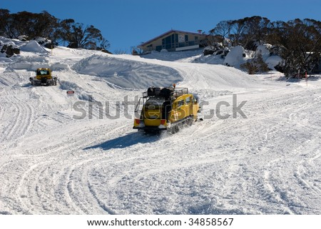 A snow grooming machine grooming the slopes, whilst a snow transport vehicle carring guests makes its way to a nearby chalet, Perisher Valley, Australia