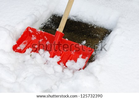 A snow shovel being used to clear a pavement - close up - stock photo