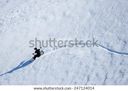 A snowboarder carves his way down a pristine back country slope in rural Lesotho. - stock photo