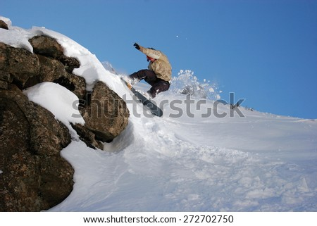 A snowboarder carves off a snow berm next to a clump of rocks on a slope in rural Lesotho. - stock photo