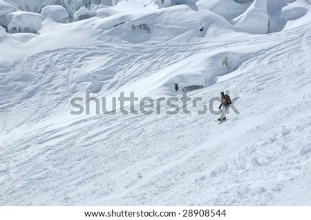 a snowboarder descends a glacier next to a large ice fall. In the background large blocks of ice, covered by fresh snow show blue ice in places
