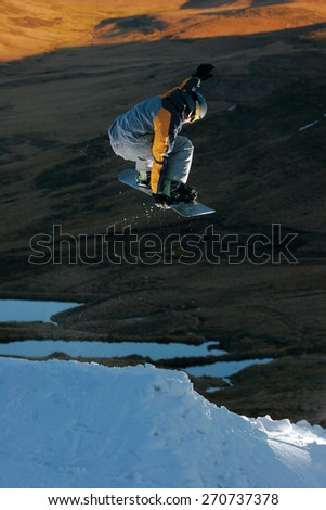 A snowboarder executes a radical aerial move. - stock photo