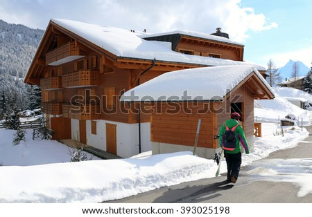 A snowboarder walks through the streets of a quaint alpine village near a ski resort in the Swiss Alps, Switzerland. - stock photo