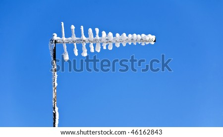A snowy antennae over blue winter sky - stock photo